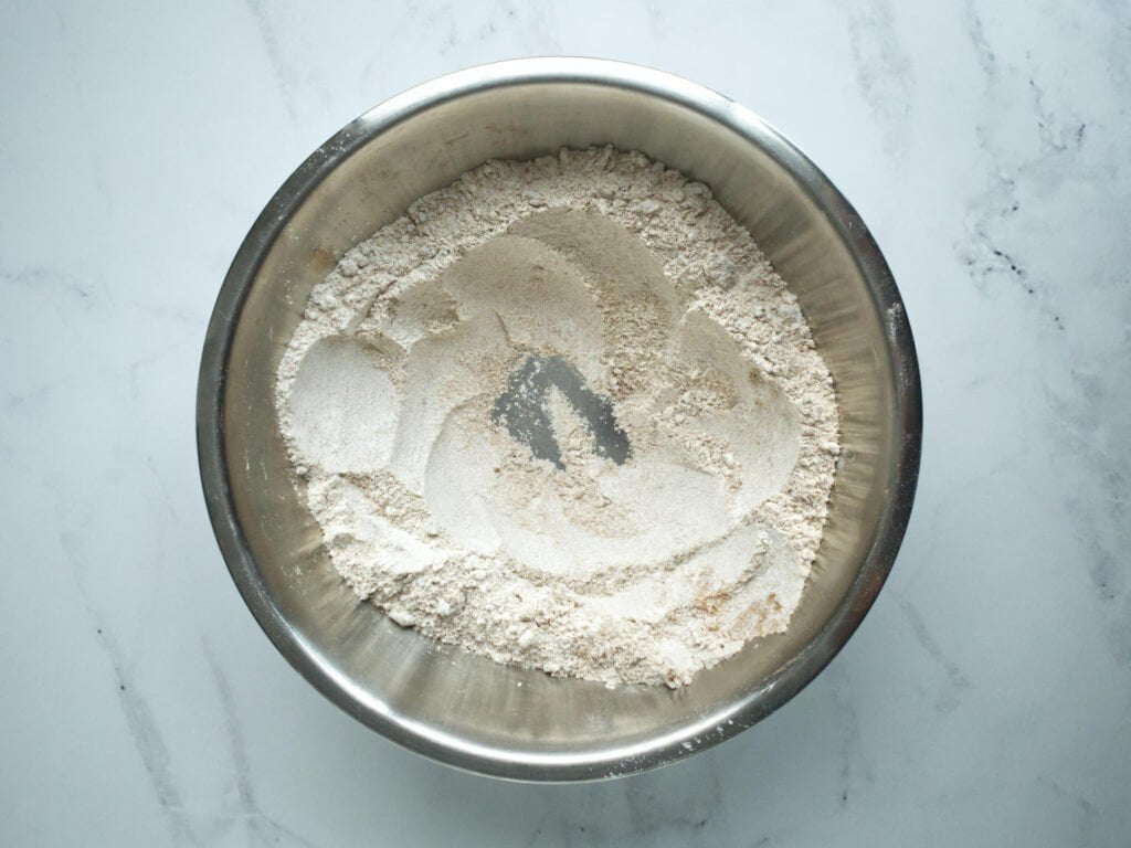 Dry ingredients in mixing bowl with a well in the centre