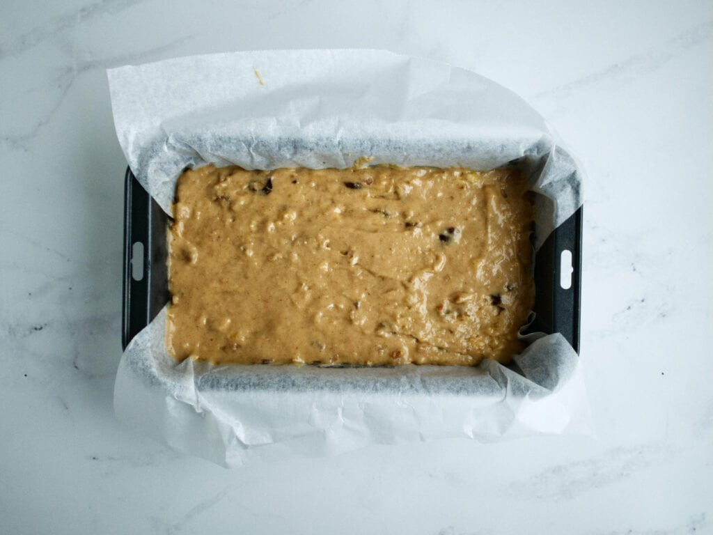 Banana bread mixture in loaf pan lined with baking paper