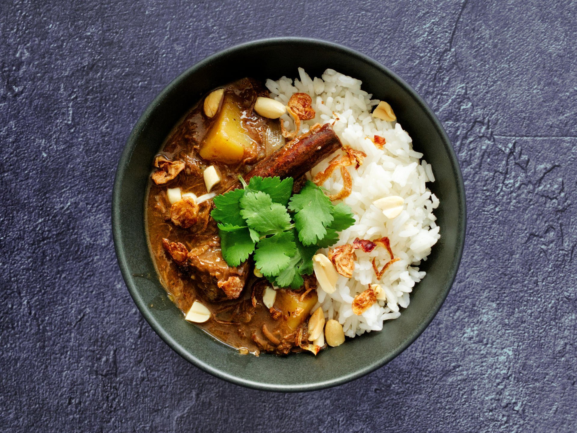 Beef massaman curry served in a bowl with rice and garnished with coriander, peanuts and dried shallots