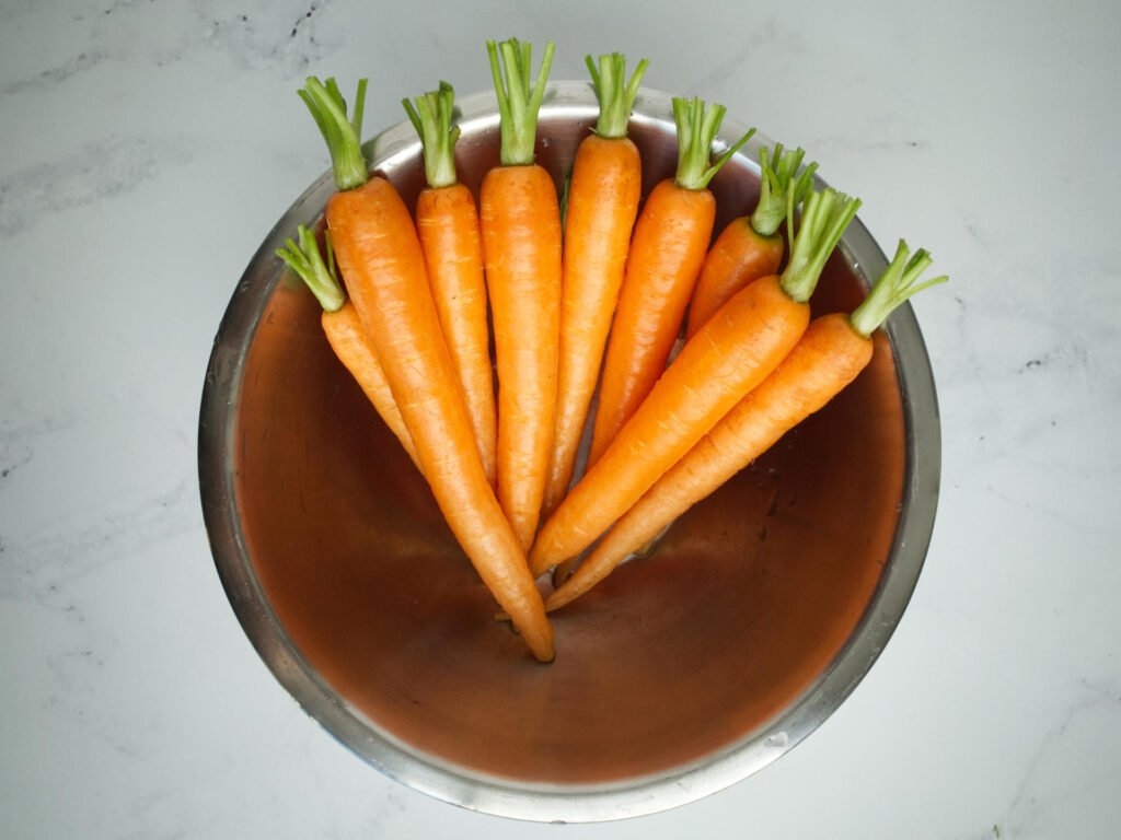 Trimmed Dutch carrots in kitchen bowl