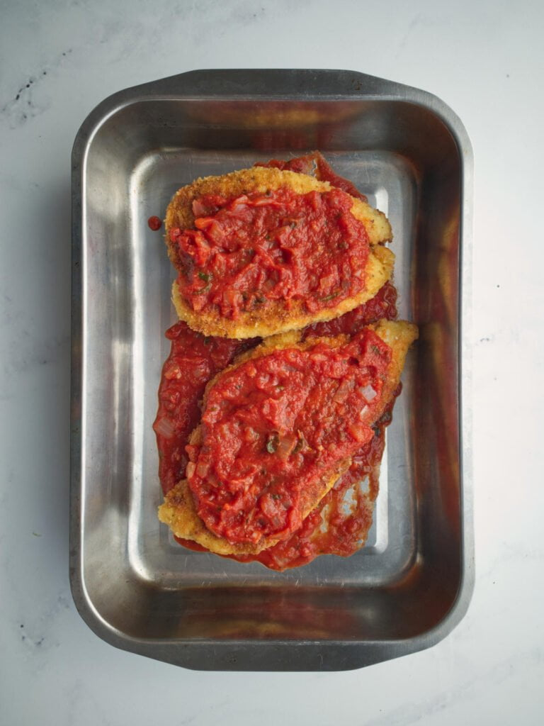 Chicken schnitzels covered in tomato sauce