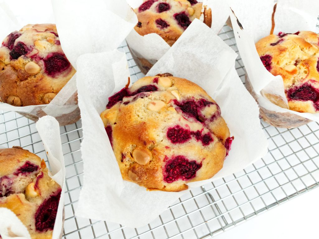 Raspberry and white chocolate muffins cooling on a wire rack