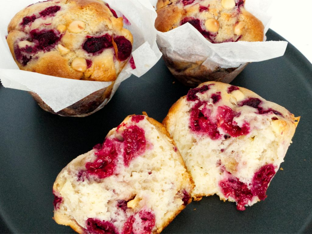 Raspberry and white chocolate muffin torn in half showing muffin filling