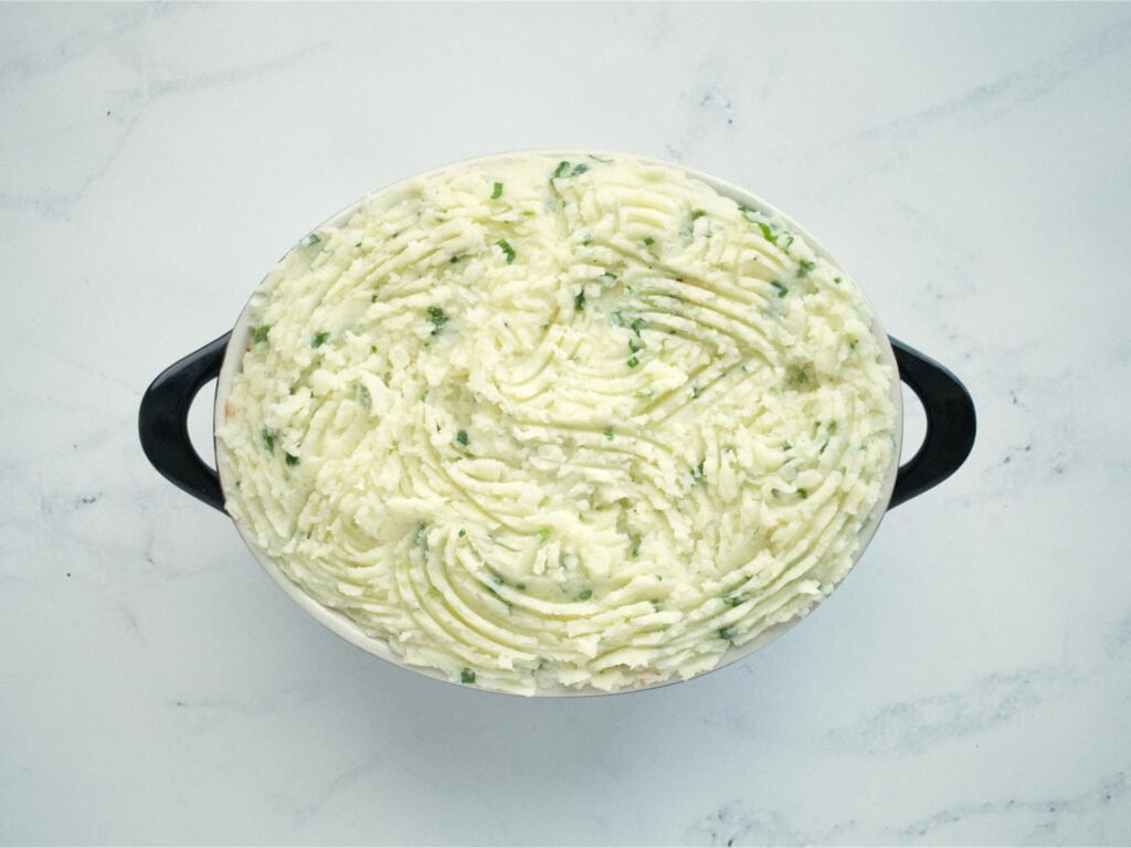Baking dish containing meat sauce covered with mashed potato
