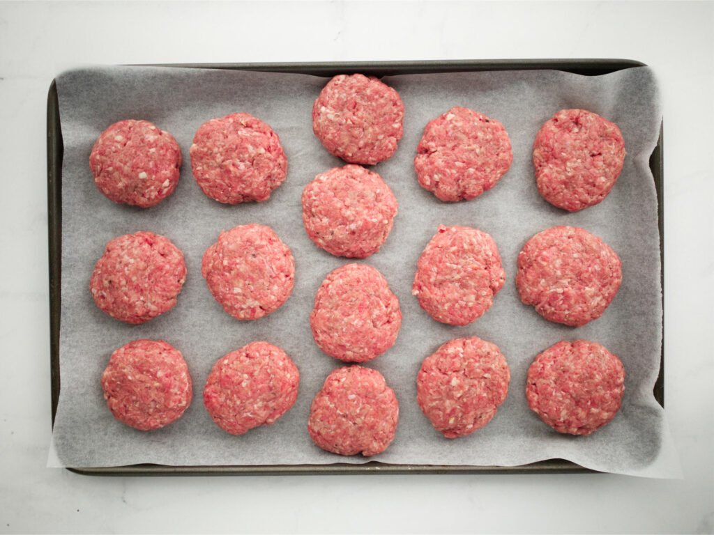 Cheeseburger slider patties on a tray ready for cooking