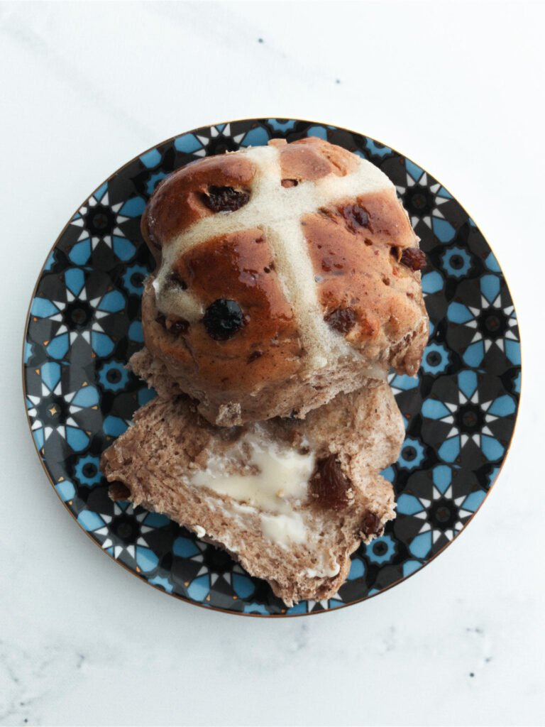 Hot cross bun served on a plate with butter