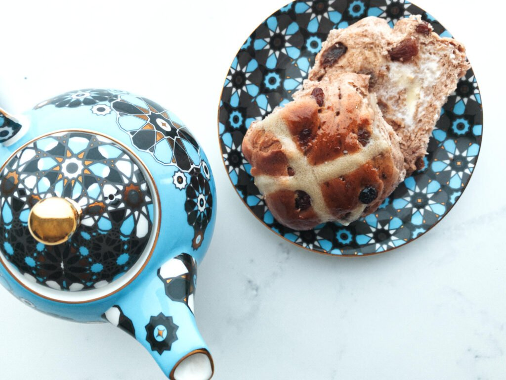 Hot cross bun on plate with lashing of butter sitting next to a blue teapot