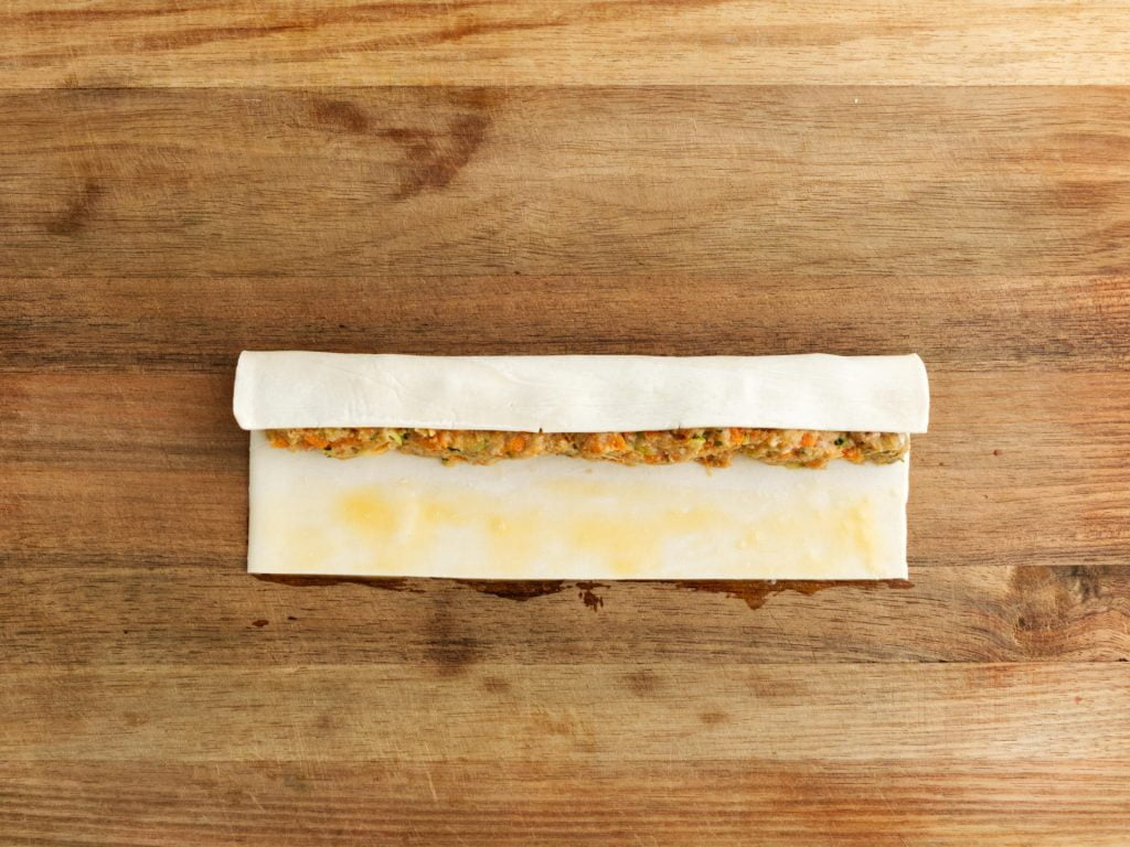 Rolling puff pastry over chicken mince
