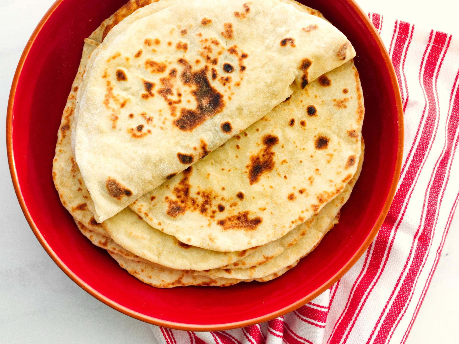 A stack of flatbreads on a red plate